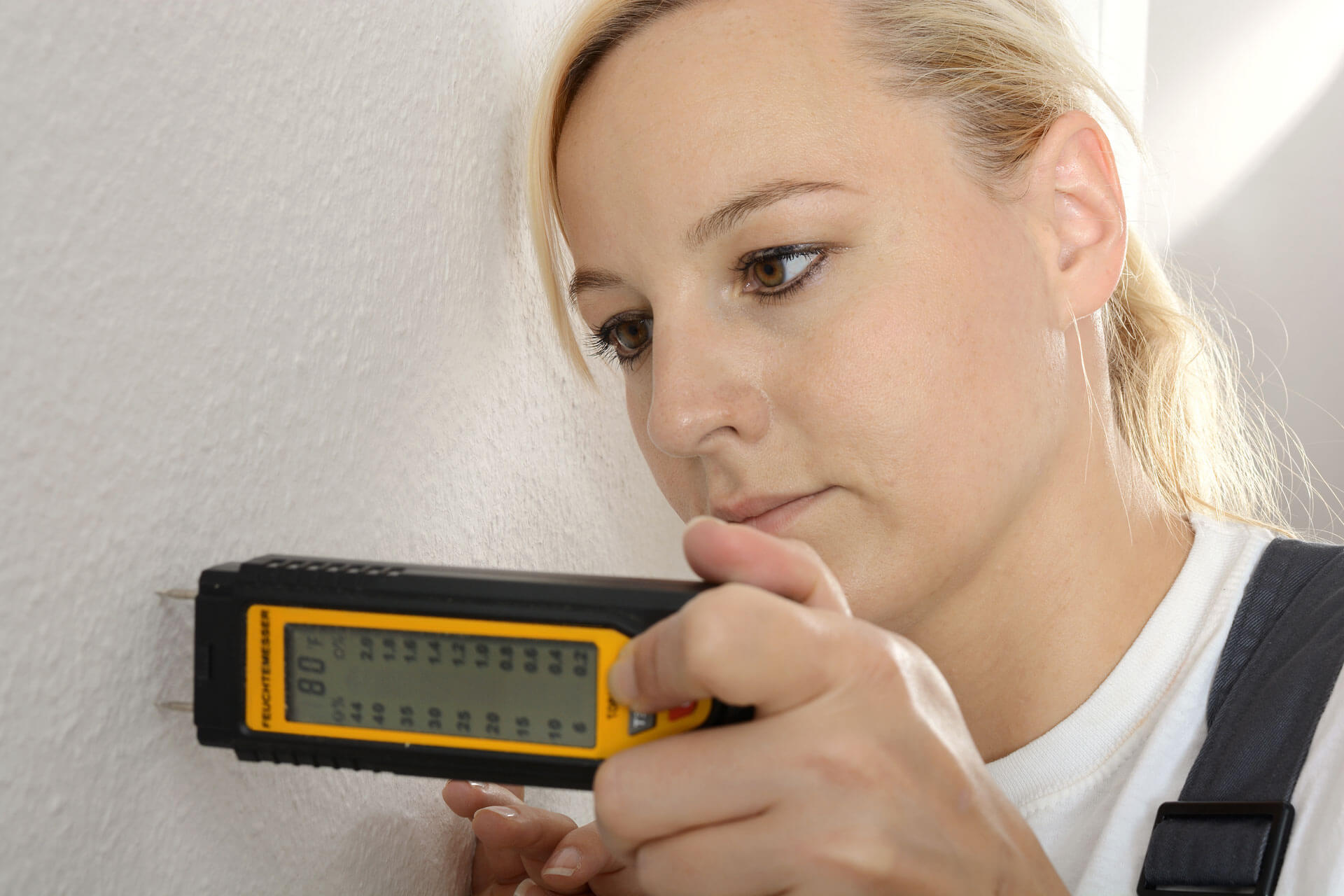 Woman conducting a moisture Test looking for mold growth conditions; Pure Mainteance Nebraska